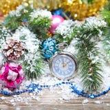 Decorazioni ed orologio di Natale nella neve Immagini Stock