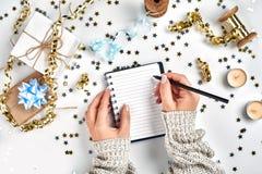 Decorazioni festive, nastri ondulati delicati, coriandoli a forma di stella metallici e taccuino con la lista di obiettivi sulla  fotografia stock libera da diritti