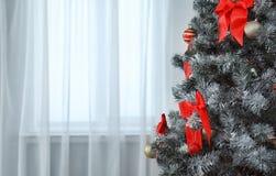 Decorazioni festive sull'albero di Natale nell'interno vivente alla moda immagini stock