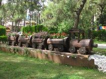Decorazioni in parco con la crescita di fiori in treno di legno fotografia stock