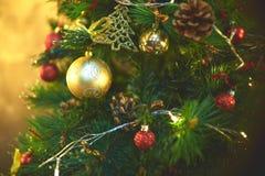 Decorazioni per un albero di Natale contro lo sfondo delle luci di una ghirlanda Fotografie Stock Libere da Diritti