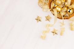 Decorazioni, stelle d'oro, palle e nastri di Natale su fondo di legno bianco molle, spazio della copia Immagini Stock