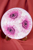 Decoupage decorated flower pattern plate on  red fabric backgrou Stock Photo