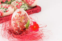 Decoupage Easter egg on red straw Stock Photography