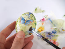 Decoupage egg. Close up of holding and painting Easter egg with decoupage technique stock photo