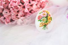 Decoupage ha decorato l'uovo di Pasqua, con i fiori rosa dei giacinti, sopra fotografia stock libera da diritti
