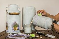 Decoupage - manos que pintan las mantequeras de leche con una esponja Imágenes de archivo libres de regalías