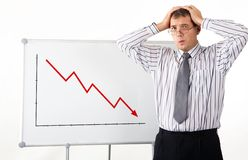 Decrease. Portrait of frustrated man touching his head with whiteboard representing decreasing graph on it Royalty Free Stock Image