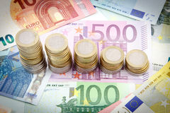 Decreasing stacks of euro coins. On euro banknotes Stock Images