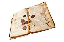 Decrepit book with copper coins Stock Photo