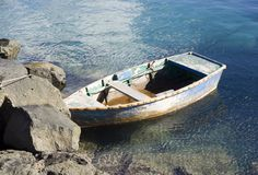 Decrepit dinghy. Old, possibly sinking, dinghy moored against rocks royalty free stock image