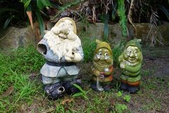 Decrepit Garden Gnomes. Old broken and stained garden gnomes recovered from overgrown garden royalty free stock photos