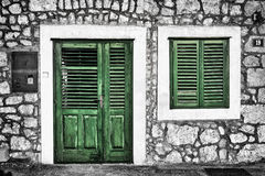 Decrepit green door and window on the Dalmatian house Stock Images