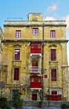 Decrepit house with new red windows Royalty Free Stock Photo