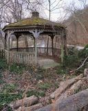 Neglected gazebo stands stolidly over canal. Decrepit and moss covered gazebo remains standing amidst ivy covered detritus of the woods.  Forgotten and alone Royalty Free Stock Images