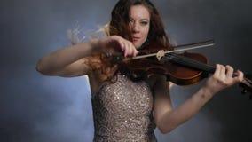 Decreto, con el fiddler largo del pelo jugando en el violín en oscuridad en humo en filarmónico almacen de metraje de vídeo