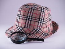 Dectectives tools. Old style patterned felt hat with a magnifying glass resting on it Royalty Free Stock Image