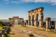 The Decumanus Maximus, Volubilis. The Decumanus Maximus with the Hercules Works House and the Triumphal Arch, Volubilis, Morocco Royalty Free Stock Images