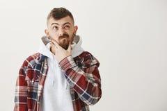 Decyzje są ciężkie robić Skołatana śliczna caucasian samiec z modnym ostrzyżeniem i odzieżową wzruszającą brodą przyglądającymi,  Obrazy Stock