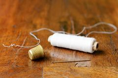 Dedal, aguja, carrete del hilo, chapa antigua por completo de grietas Fotografía de archivo libre de regalías
