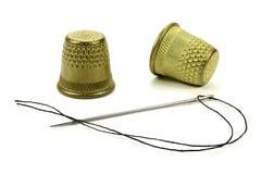 Dedales e hilo de cobre amarillo viejos con una aguja para coser en un fondo blanco Imagen de archivo libre de regalías