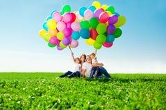 拿着五颜六色的气球的愉快的家庭。妈妈, ded和两daughte 图库摄影
