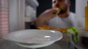Dedicado ao homem do fast food que come o hamburguer do refrigerador na noite, estilo de vida insalubre imagem de stock
