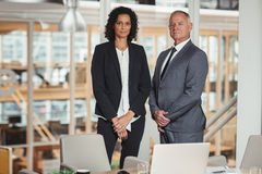 They are dedicated company executives. Portrait of a mature businessman and young colleague standing together in an office boardroom stock image
