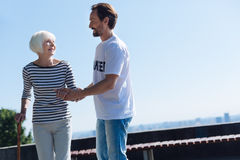 Dedicated gallant man taking positive senior lady on a stroll. I can walk a mile with you. Pretty adorable aged women having an active lifestyle and asking the Stock Photos