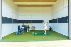 Dedicated golf coach using modern equipment while teaching a young woman royalty free stock photos