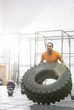Dedicated man flipping tire in crossfit gym Royalty Free Stock Image