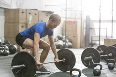 Dedicated man lifting barbell in crossfit gym Stock Photo