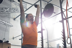 Dedicated man lifting barbell in crossfit gym royalty free stock image