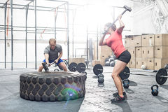 Dedicated man and woman hitting tire with sledgehammer in crossfit gym stock photos