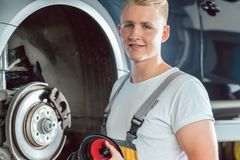 Dedicated mechanic working in a modern automobile repair shop wi royalty free stock photography