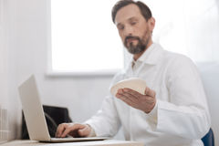 Dedicated observant plastic surgeon studying new implant. Checking the quality. Clever qualified young specialist receiving an experimental sample for testing it Royalty Free Stock Images