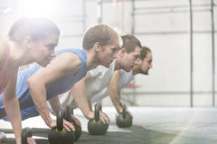 Dedicated people doing pushups with kettlebells at crossfit gym royalty free stock images
