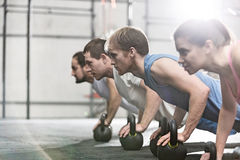 Dedicated people doing pushups with kettlebells at crossfit gym stock photos