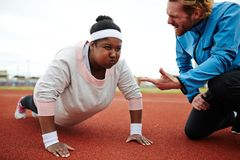 Difficult push-ups. Dedicated sport trainer encouraging overweight young women try harder while practicing push-ups Royalty Free Stock Photography