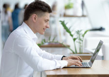 Dedicated stylish young businessman working on project in cozy small cafe. Portrait Royalty Free Stock Image