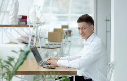 Dedicated stylish young businessman working on project in cozy small cafe. Portrait Royalty Free Stock Images