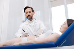 Dedicated trained doctor carefully putting guidelines for future cuts Royalty Free Stock Photography