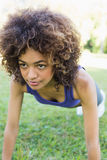 Dedicated woman doing push ups in park Stock Image