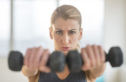 Dedicated Woman Lifting Dumbbells At Health Club Stock Photos