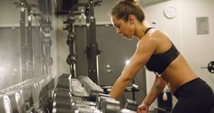 Dedicated woman training and lifting weights in fitness gym. Weights training woman in fitness gym lifting weights and showing strong body. Slow motion workout stock video footage