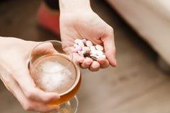 Dedichi il problema, la donna con le pillole e la birra in mani immagini stock libere da diritti