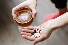 Dedichi il problema, la donna con le pillole e la birra in mani immagini stock