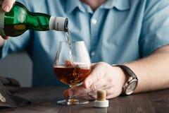 Dedichi l'edizione, uomo si versa un whiskey immagini stock