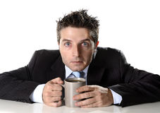 Dedichi l'uomo d'affari che giudica la tazza di caffè ansiosa e pazza nella dipendenza della caffeina immagini stock libere da diritti