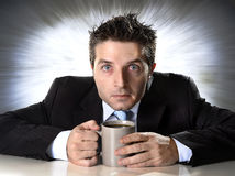 Dedichi l'uomo d'affari che giudica la tazza di caffè ansiosa e pazza nella dipendenza della caffeina fotografia stock libera da diritti